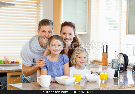 Family together with breakfast standing behind the kitchen count stock photo, Young family together with breakfast standing behind the kitchen counter by Wavebreak Media
