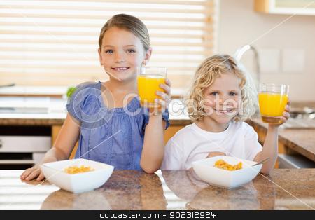 Siblings in the kitchen rising their glasses stock photo, Siblings in the kitchen rising their glasses of orange juice by Wavebreak Media