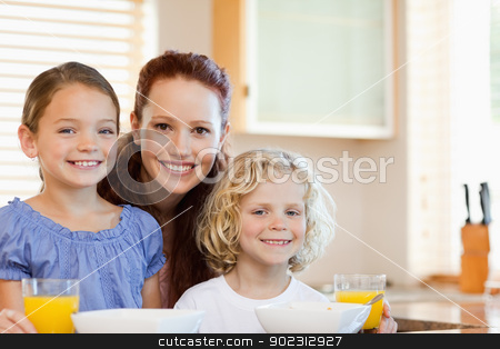Smiling mother with her children in the kitchen stock photo, Smiling mother together with her children in the kitchen by Wavebreak Media