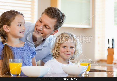 Father with his children behind the kitchen counter stock photo, Father together with his children behind the kitchen counter by Wavebreak Media