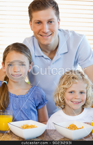 Father with his children and cereals stock photo, Father together with his children and cereals by Wavebreak Media