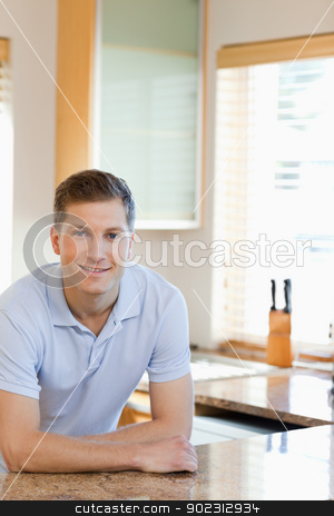 Man leaning against the kitchen counter stock photo, Smiling man leaning against the kitchen counter by Wavebreak Media