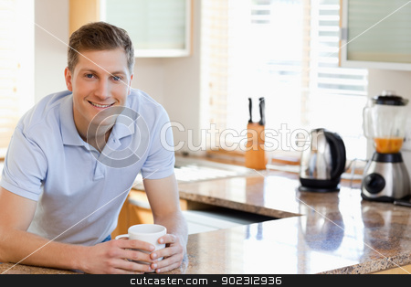 Male leaning against the kitchen counter stock photo, Smiling male leaning against the kitchen counter by Wavebreak Media