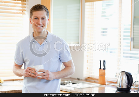 Man with cup in the kitchen stock photo, Man with white cup in the kitchen by Wavebreak Media