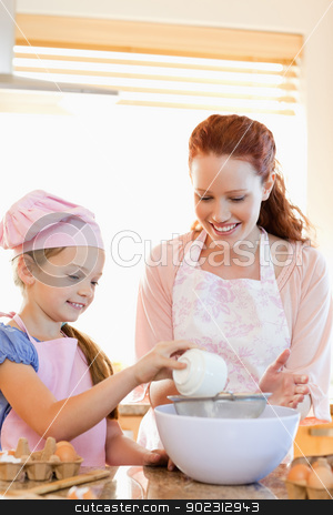 Cheerful mother and daughter preparing dough stock photo, Cheerful mother and daughter preparing dough together by Wavebreak Media