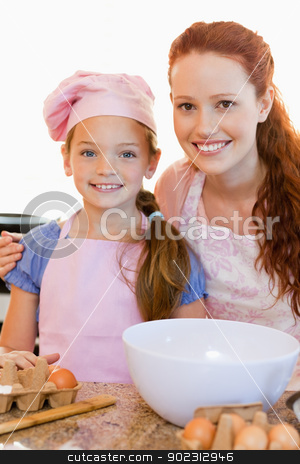 Mother and daughter with ingredients for cookies stock photo, Smiling mother and daughter with ingredients for cookies by Wavebreak Media