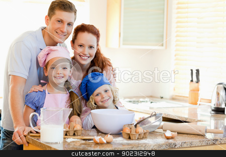 Family with baking ingredients behind the kitchen counter stock photo, Family together with baking ingredients behind the kitchen counter by Wavebreak Media