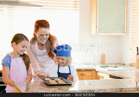 Mother presenting finished cookies to her children stock photo, Smiling mother presenting finished cookies to her children by Wavebreak Media