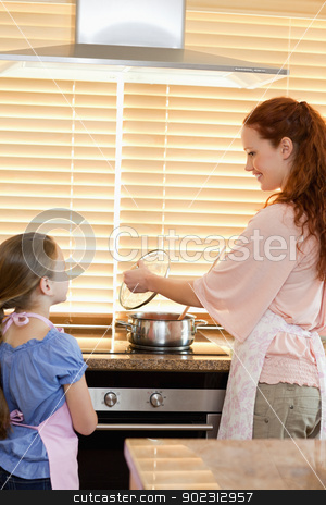 Mother and daughter preparing meal stock photo, Mother and daughter preparing meal together by Wavebreak Media