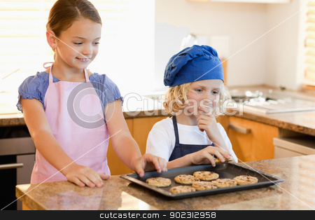 Siblings stealing cookies stock photo, Siblings stealing cookies off the kitchen counter by Wavebreak Media