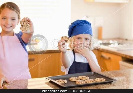 Siblings showing their cookies stock photo, Siblings showing their cookies in the kitchen by Wavebreak Media