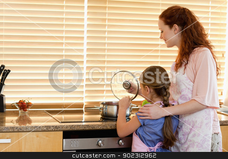 Mother and daughter cooking a meal stock photo, Mother and daughter cooking a meal together by Wavebreak Media