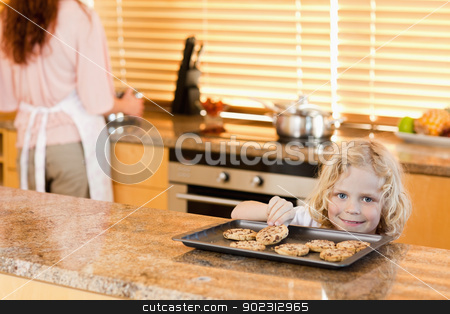 Boy stealing a cookie while his mother is not watching stock photo, boy stealing a cookie while is mother is not watching by Wavebreak Media