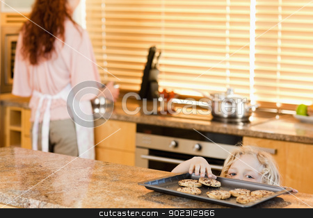 Boy sneaking up to cookies stock photo, Cheeky boy sneaking up to cookies by Wavebreak Media