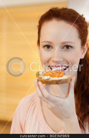 Woman having a slice of bread stock photo, Woman having a slice of bread with tomato by Wavebreak Media