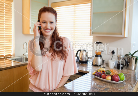 Smiling woman talking on the phone in the kitchen stock photo, Happy smiling woman talking on the phone in the kitchen by Wavebreak Media