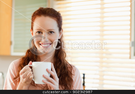 Smiling woman with cup stock photo, Smiling woman with cup in her hands by Wavebreak Media