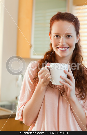 Smiling woman with cup in her hands stock photo, Smiling woman with white cup in the hands by Wavebreak Media