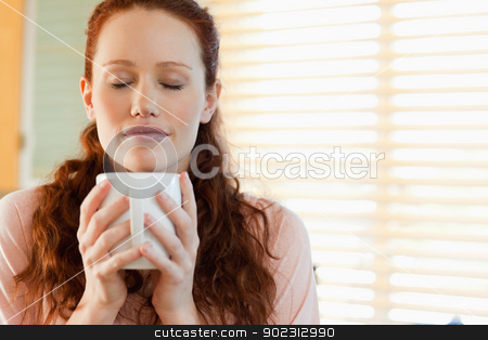 Woman enjoys the smell of her coffee stock photo, Woman enjoys the smell of her fresh coffee by Wavebreak Media