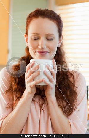 Joyful woman holding a cup of coffee stock photo, Joyful woman holding a cup of hot coffee by Wavebreak Media