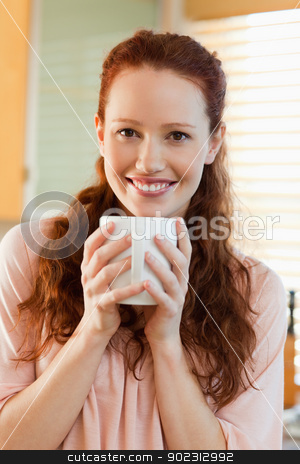 Smiling woman with her cup of coffee stock photo, Smiling young woman with her cup of coffee by Wavebreak Media