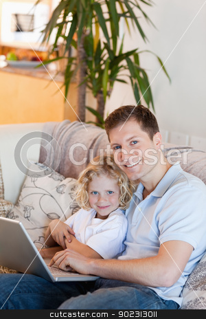 Father and son together with laptop stock photo, Father and son together with laptop on the sofa by Wavebreak Media
