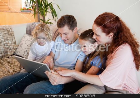Family using notebook on the sofa stock photo, Family using notebook on the sofa together by Wavebreak Media