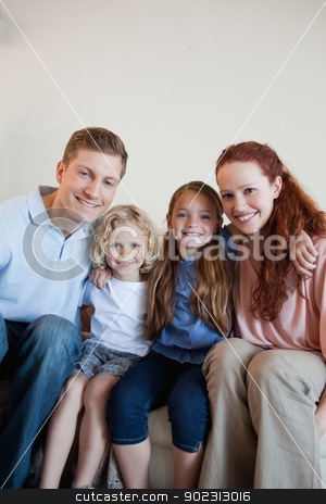 Cheerful family on the sofa stock photo, Cheerful smiling family on the sofa by Wavebreak Media