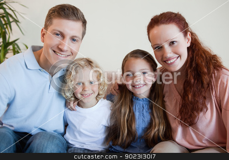 Family sitting on the sofa together stock photo, Smiling family sitting on the sofa together by Wavebreak Media
