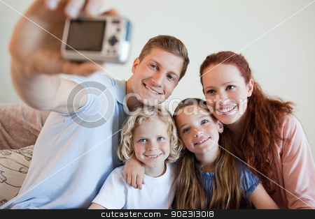 Father taking a family picture stock photo, Father taking a family picture on the sofa by Wavebreak Media