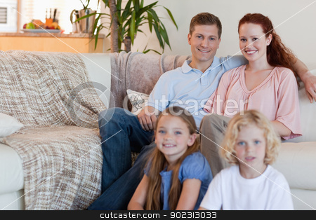 Family sitting in the living room stock photo, Young family sitting in the living room by Wavebreak Media