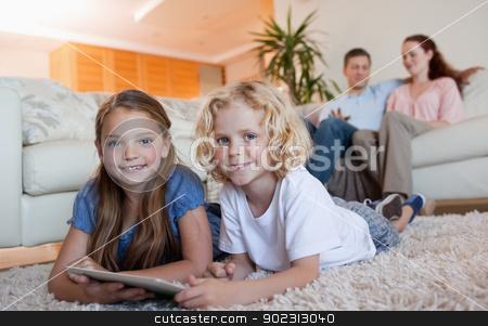 Siblings on the carpet using tablet stock photo, Siblings on the carpet using tablet together by Wavebreak Media