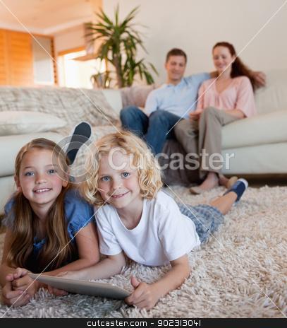 Children on the carpet using tablet stock photo, Children on the carpet using tablet together by Wavebreak Media