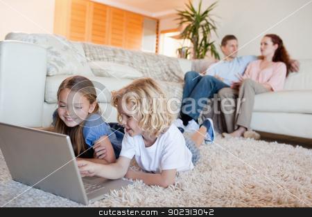 Siblings using laptop in the living room stock photo, Siblings using laptop in the living room together by Wavebreak Media