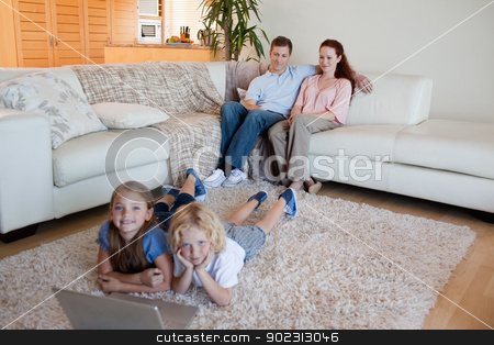 Brother and sister with notebook on the carpet stock photo, Brother and sister together with notebook on the carpet by Wavebreak Media