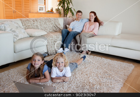 Siblings with laptop on the floor stock photo, Siblings together with laptop on the floor by Wavebreak Media