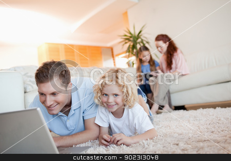 Father and son with laptop on the floor stock photo, Father and son together with laptop on the floor by Wavebreak Media