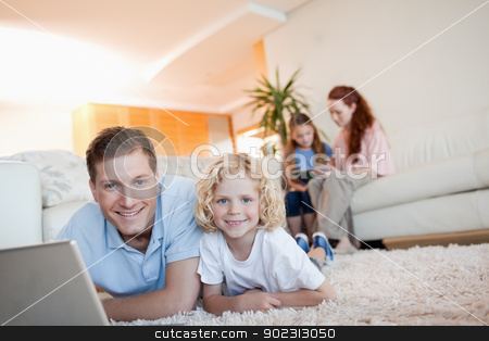 Father and son using the internet in the living room stock photo, Father and son using the internet together in the living room by Wavebreak Media