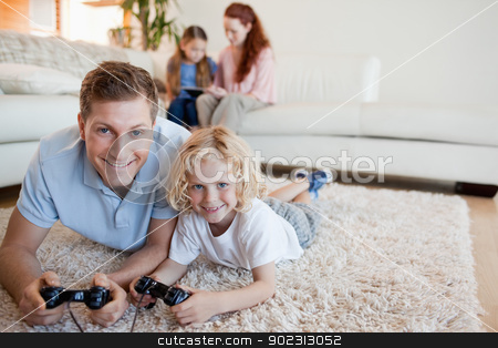 Father and son on the floor playing video games stock photo, Father and son on the floor playing video games together by Wavebreak Media