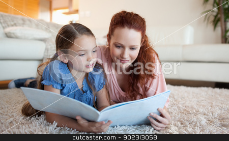 Mother and daughter looking at a magazine stock photo, Mother and daughter looking at a magazine together by Wavebreak Media