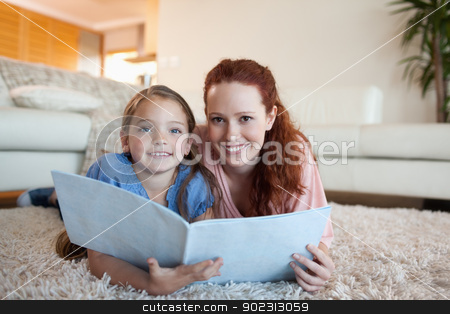 Mother and daughter looking at periodical stock photo, Mother and daughter looking at periodical together by Wavebreak Media