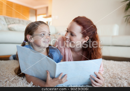 Mother and daughter with periodical on the floor stock photo, Mother and daughter together with periodical on the floor by Wavebreak Media