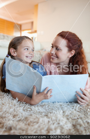 Mother and daughter on the floor looking at magazine stock photo, Mother and daughter on the floor looking at magazine together by Wavebreak Media