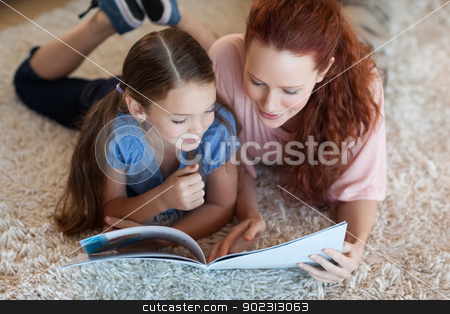 Mother and daughter on the carpet reading stock photo, Mother and daughter on the carpet reading together by Wavebreak Media