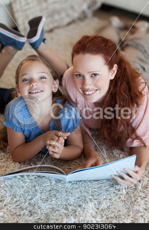 Mother and daughter on the floor reading stock photo, Mother and daughter on the floor reading together by Wavebreak Media