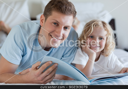 Father and son looking at magazine stock photo, Father and son looking at magazine together by Wavebreak Media