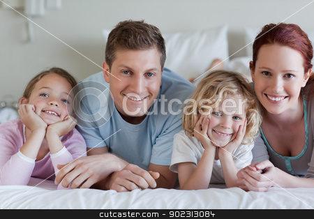 Family lying on the bed stock photo, Family lying on the bed together by Wavebreak Media