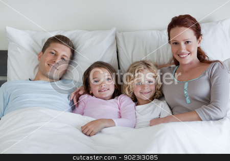 Family sharing the bed stock photo, Young family sharing the bed by Wavebreak Media