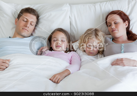 Adorable family sleeping in the bed together stock photo, Adorable young family sleeping in the bed together by Wavebreak Media