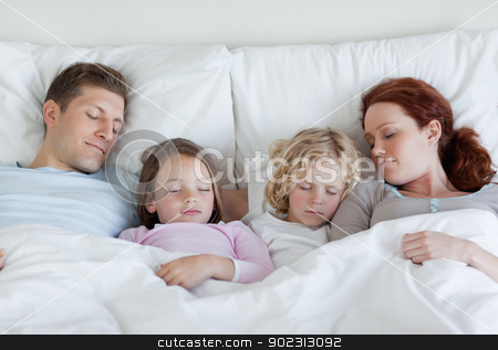 Family taking a nap together stock photo, Young family taking a nap together by Wavebreak Media